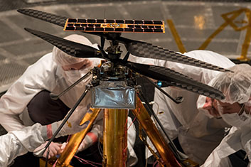 Members of the NASA Mars Helicopter team inspect the flight model inside the Space Simulator